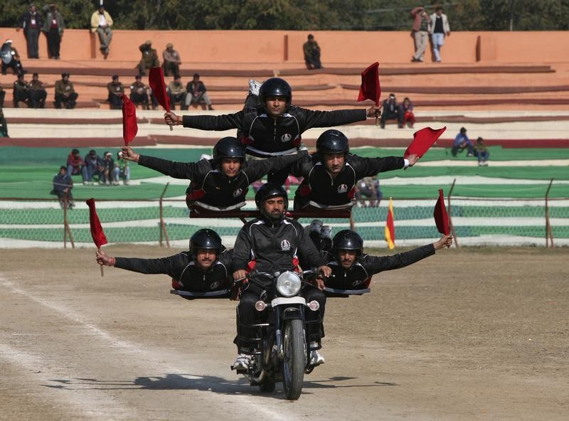 Indian policemen perform a stunt on a motorcycle during the Republic Day parade in Jammu January 26, 2013.