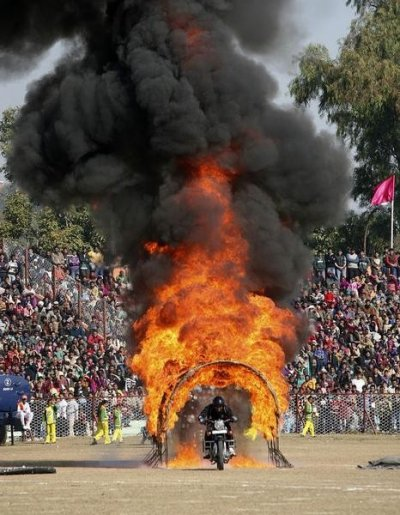 An Indian policeman performs a stunt on his motorcycle during the Republic Day parade in Jammu January 26, 2013. India celebrated its 64th Republic Day on Saturday.