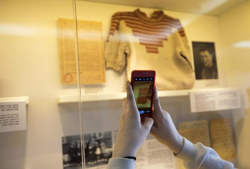 Grand-daughter of Holocaust survivor Gucia Teiblum, takes a photograph of a sweater knitted by her grandmother at a Nazi concentration camp, during the opening of a new display at the Yad Vashem Holocaust History Museum in Jerusalem January 27, 2013. quo
