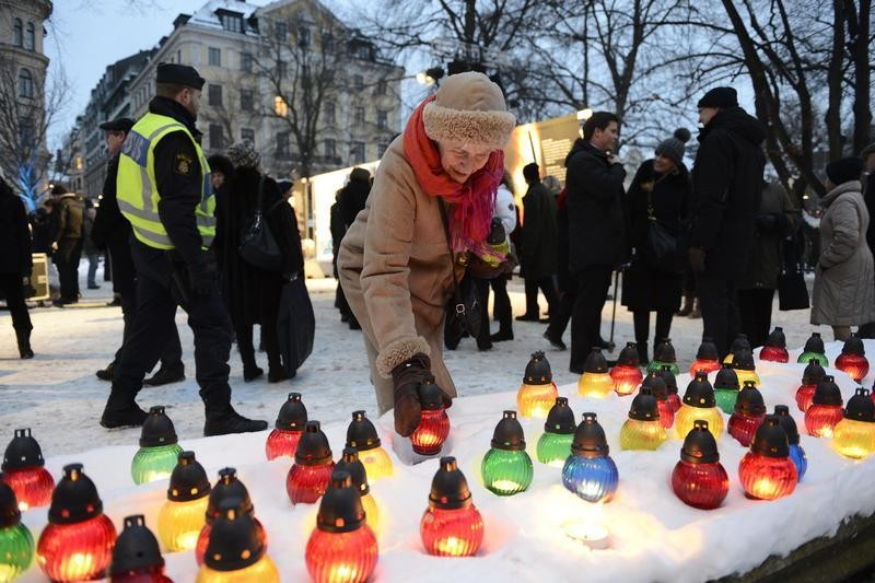 A woman lights a candle during a memorial ceremony for International Holocaust Remembrance Day at Raoul Wallenberg Square in Stockholm in this January 27, 2013 picture taken by Scanpix Sweden.