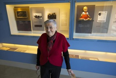 Tzvia Shkolnik, a friend of late Holocaust survivor Edit Faber, poses for a photograph near a doll which had been hidden with Faber during World War Two, during the opening of a new display at the Yad Vashem Holocaust History Museum in Jerusalem January 2
