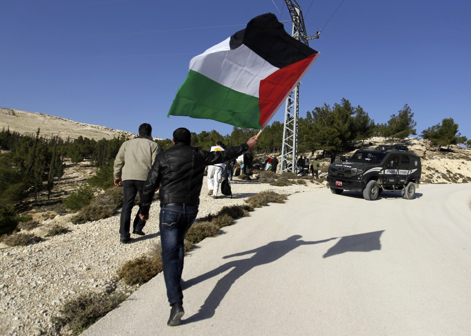 "A Palestinian protester holds a flag as he arrives at an area known as ""E1"", which connects the two parts of the Israeli-occupied West Bank"