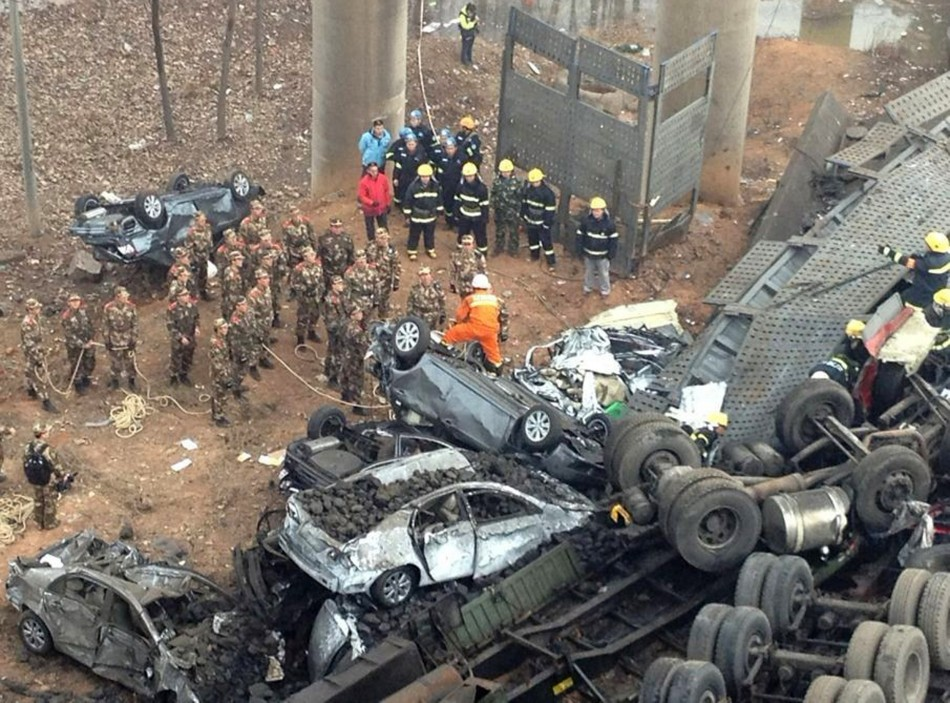 Rescuers look for survivors near the wreckage of vehicles after a expressway bridge partially collapsed on the Lianhuo highway in Mianchi county, Henan province (Reuters)
