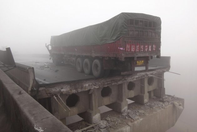 A truck stops near a section of the partially collapsed expressway bridge (Reuters)