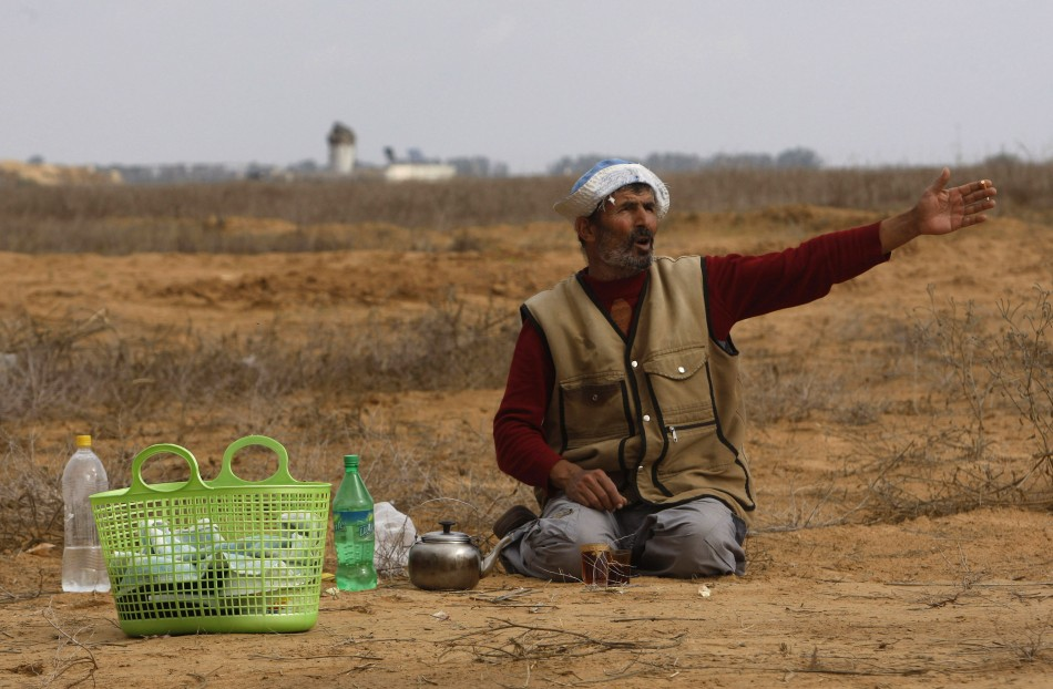 A Palestinian farmer gestures as an Israeli watchtower (rear) is seen near the fence between Israel and the southern Gaza Strip November 24, 2012.