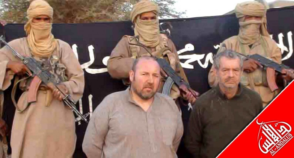 French nationals Philippe Verdon and Serge Lazarevic, who are being held hostage by Al Qaeda, are seen surrounded by masked men holding guns in an undisclosed location in Mali