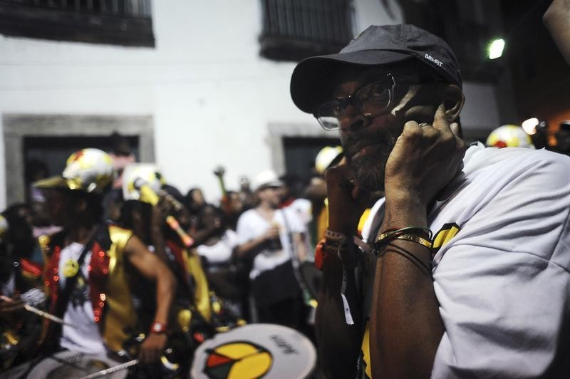 American movie director Spike Lee covers his ears as he directs the filming of Afro-Brazilian cultural group Olodum as part of his documentary project titled Go Brazil Go, during a Carnival street party in Salvador da Bahia, February 8, 2013.