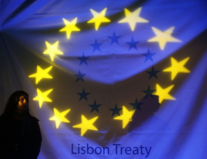 A woman stands in front of a banner displaying the stars of the European Union flag before a ceremony to mark the start of the European Union?s Lisbon reform treaty in Lisbon December 1, 2009.