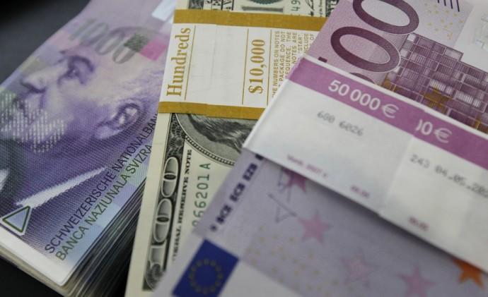 Stacks of Swiss franc, Euro and dollar banknotes