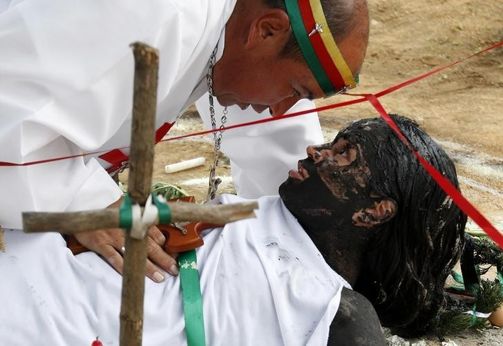 """Hermes Cifuentes, who is also known as """"Brother Hermes"""", performs an exorcism on Gisela Marulanda, 23, who claims to be possessed by spirits"""