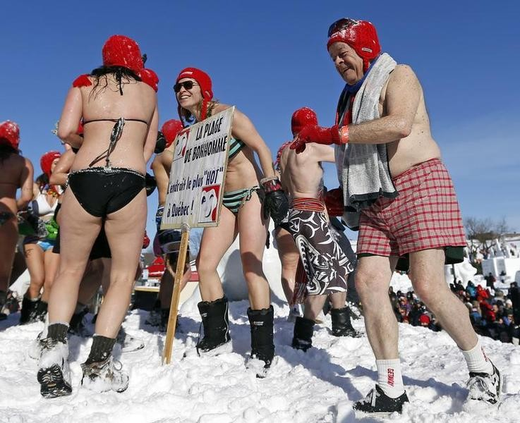 People play in the snow during the snow bath at the Quebec Winter Carnival on the Plains of Abraham in Quebec City, February 16, 2013. The sign reads Bonhommes beach, the hottest place in Quebec.