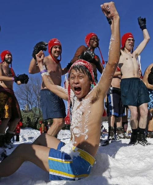 Yohei Oyoshi, a journalist from Japan, reacts after being covered with snow during the snow bath at the Quebec Winter Carnival on the Plains of Abraham in Quebec City, February 16, 2013.