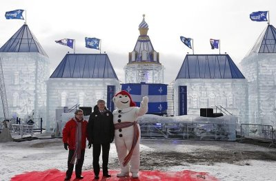 Canadas Prime Minister Stephen Harper C and Quebecs Mayor Regis Labeaume L pose for a photo with Bonhomme Carnaval, the official mascot of the Quebec Winter Carnival, on the Plains of Abraham in Quebec City, February 1, 2013.