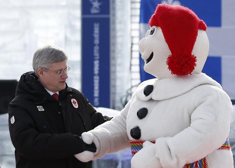 Canadas Prime Minister Stephen Harper L shakes hands with Bonhomme Carnaval, the official mascot of the Quebec Winter Carnival, on the Plains of Abraham in Quebec City, February 1, 2013.