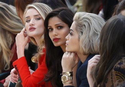 Model and actress Rosie Huntington-Whiteley L, actress Freida Pinto C and singer Rita Ora watch the presentation of the Burberry Prorsum AutumnWinter 2013 collection during London Fashion Week, February 18, 2013.
