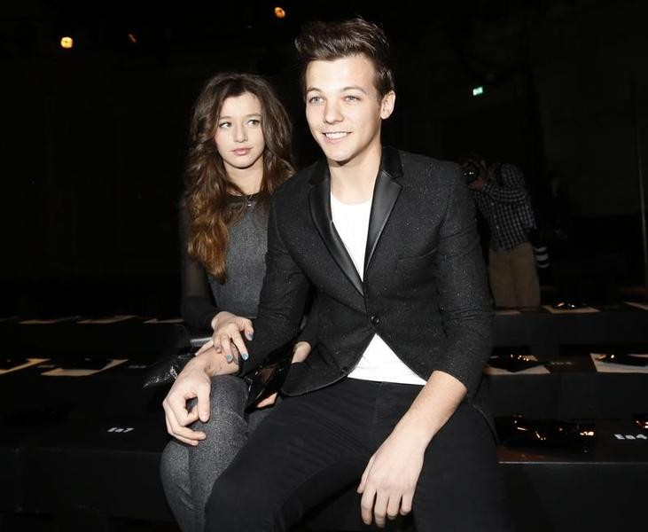 Performer Louis Tomlinson from One Direction sits with his friend in the front row at the Unique for Topshop Autumn/Winter 2013 collection during London Fashion Week, February 17, 2013.