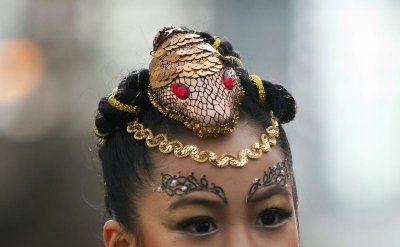 A girl wearing a hair piece shaped like a snake walks down a street during the Chinese New Year parade in Vancouver, British Columbia February 17, 2013. According to the Chinese zodiac, the Lunar New Year began on February 10 and marks the start of the Ye