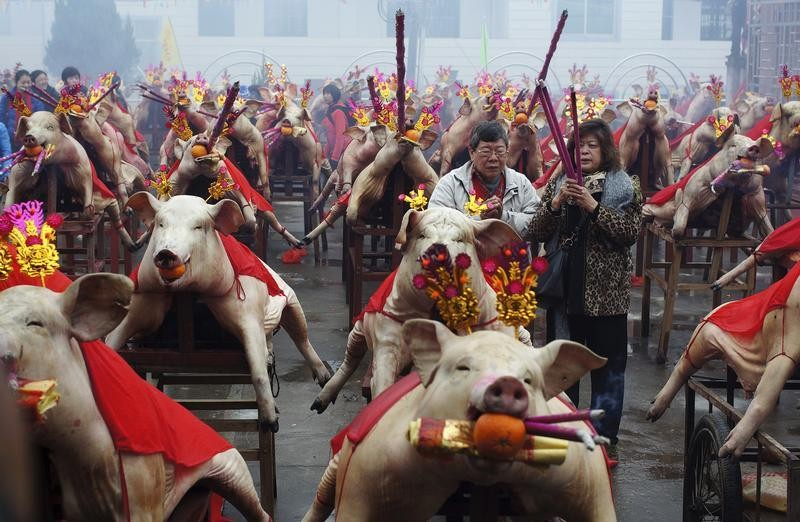 Visitors pray among slaughtered pigs holding incenses and tangerines in their mouths as offering during a Spring Festival praying ceremony in Nanan, Fujian province February 14, 2013. The Lunar New Year, or Spring Festival, began on February 10 and marks