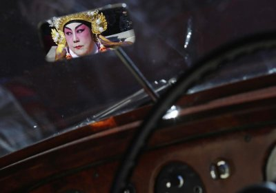 A woman dressed in traditional costume is reflected in the mirror of a 1956 Bentley as she takes part in the 14th Annual Chinatown Lunar New Year Parade in New York, February 17, 2013. This year celebrates the year of the snake in the Chinese calendar.