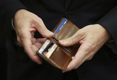 Treasury Secretary Geithner puts a piece of foreign currency back in his wallet during a break in his testimony on Capitol Hill in Washington