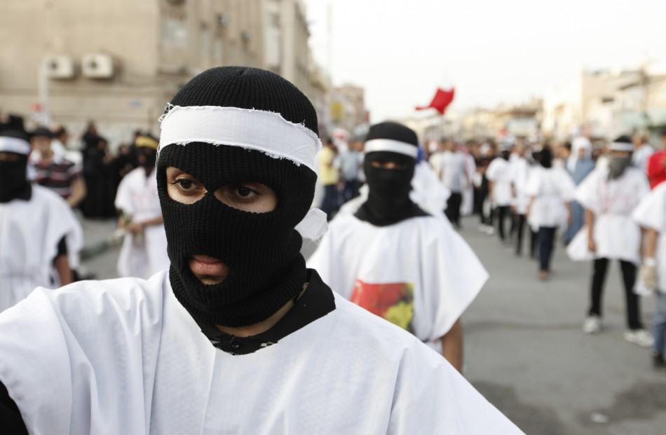 Protesters wearing burial shrouds take part in a procession during a visit to the grave of a 16-year-old youth killed by Bahraini security forces in clashes on February 14
