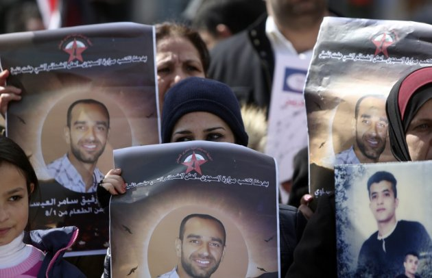 Palestinians hold placards depicting prisoner Samer al-Issawi, who has been on hunger strike for 209 days, during a protest in the West Bank city of Ramallah, calling for the release of Palestinian prisoners from Israeli jails, February 17, 2013. (Photo: