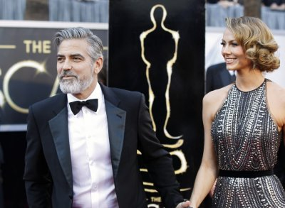 George Clooney, producer of best picture nominated film Argo, arrives at the 85th Academy Awards with his girlfriend Stacy Keibler, in Hollywood, California February 24, 2013.