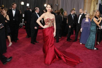 Actress Olivia Munn wears a red and gold Marchesa gown arrives at the 85th Academy Awards in Hollywood, California February 24, 2013.