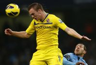 Alex Pearce heads the ball away from Carlos Tevez