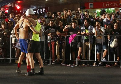 Spectators cheers as members of the group Gay Tradies kiss as they participate in the 35th annual Sydney Gay and Lesbian Mardi Gras parade March 2, 2013.