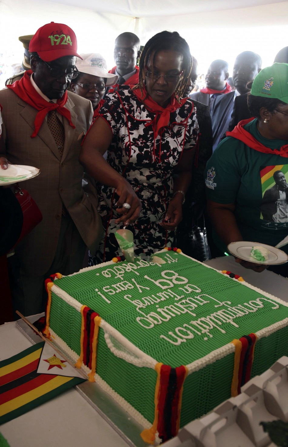 Zimbabwes President Robert Mugabe looks at his wife Grace cutting a cake during an event marking his 89th birthday at Chipadze stadium in Bindura, about 90 km 56 miles north of the capital Harare March 2, 2013. Addressing a rally to mark his 89th