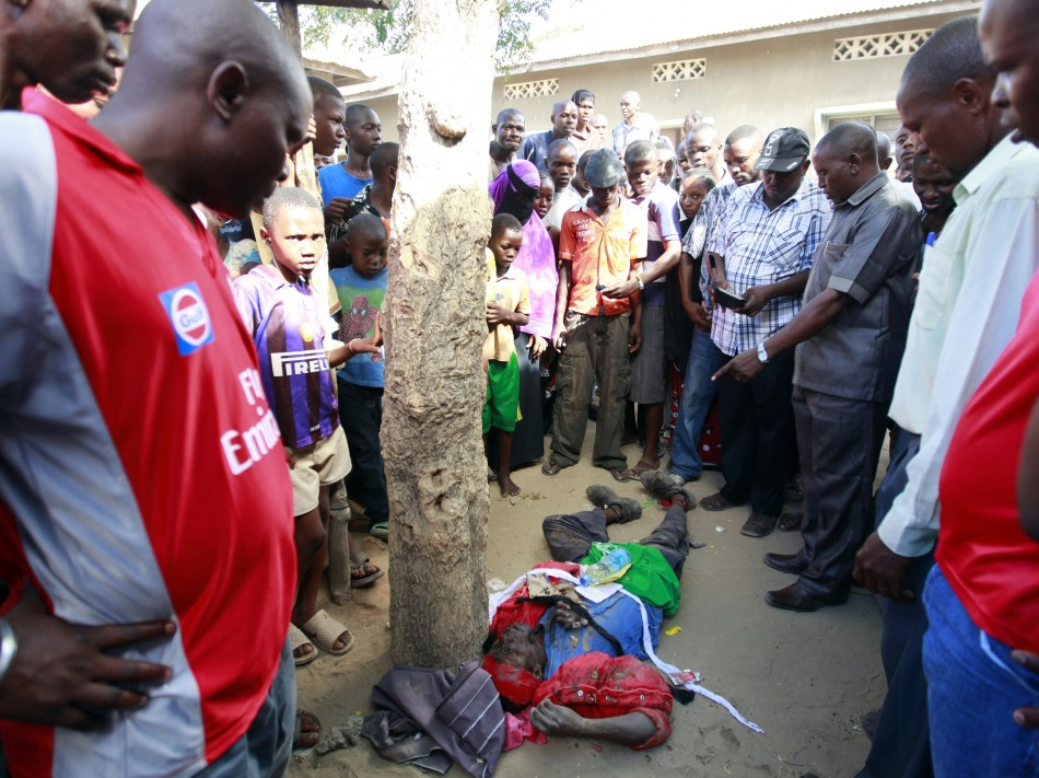 Kenyans look at the body of a member of the Mombasa Republican Council MRC who was shot dead at Mishomoroni area of the Kenyan Coast March 4, 2013