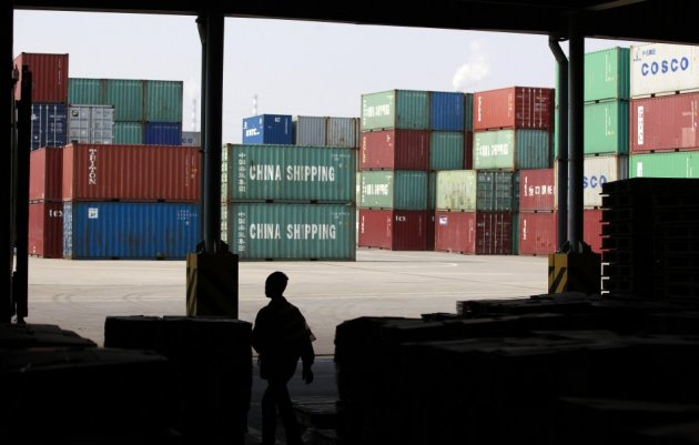 A worker walks in a shipping container area at the Port of Shanghai