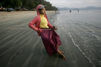 A woman pulls on a fishing net line on Maungmagan beach near the town of Dawei in southern Myanmar November 19, 2011. Picture taken November 19, 2011.