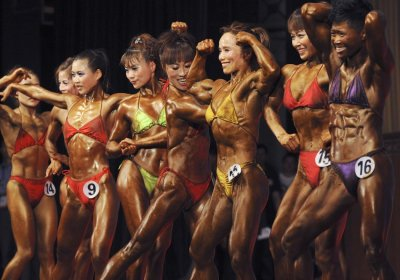 Participants pose on stage during the bodybuilding competition at the 4th All-China Games in Anhui Grand Theatre in Hefei, Anhui province, May 22, 2010.