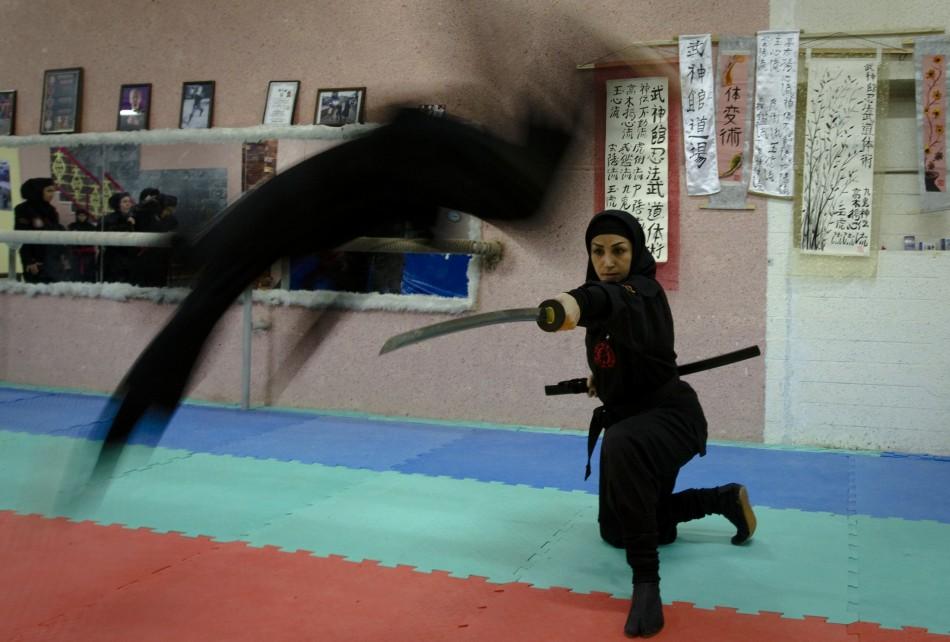 A Ninjutsu practitioner jumps over a sword as members of various Ninjutsu schools showcase their skills to the media in their gym at Karaj, 45 km 28 miles northwest of Tehran February 13, 2012.