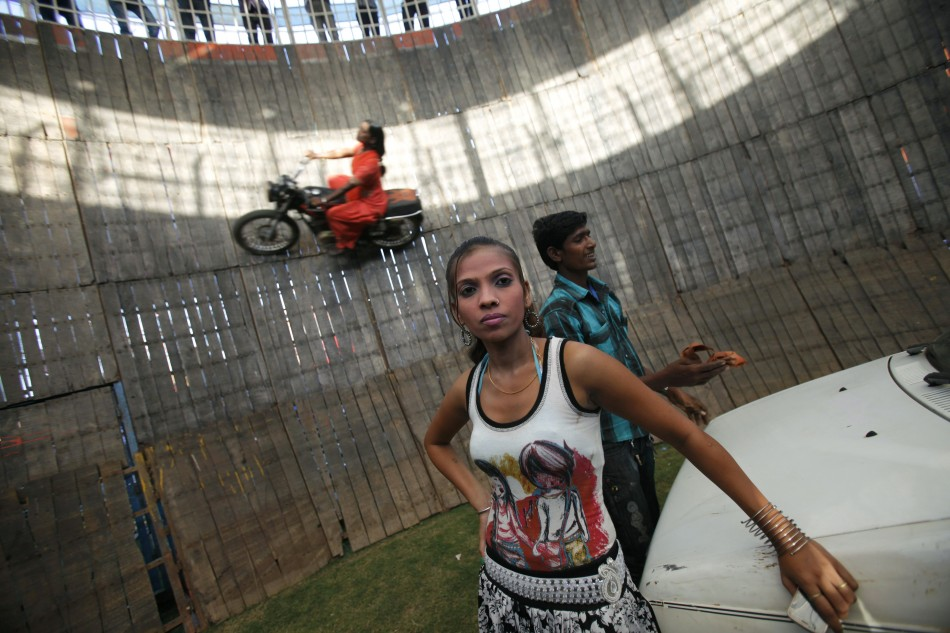 A team member front is seen as Salma Pathan, 21, a performer from the western Indian state of Maharashtra, performs a stunt as she rides a bike on the walls of the Well of Death, one of the attractions at Ramlila fair, in the old quarters of