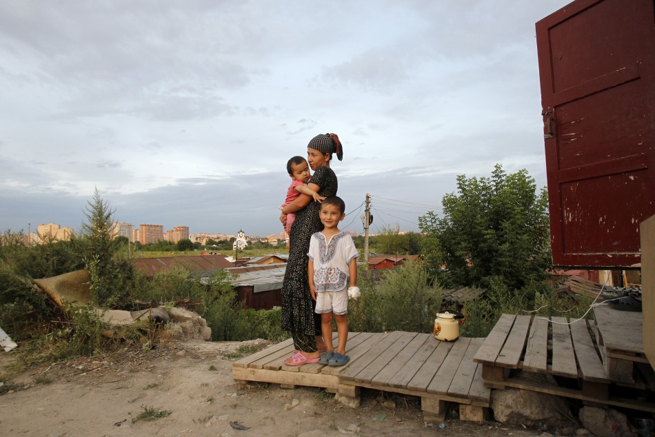 A migrant woman stands with her daughter and nephew outside their shelter on the outskirts of Moscow July 26 2011.