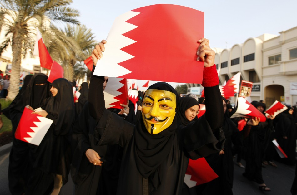 A female protester, wearing a Guy Fawkes mask, holds a Bahraini paper flag in an anti-government rally in Budaiya, west of Manama March 1, 2013.
