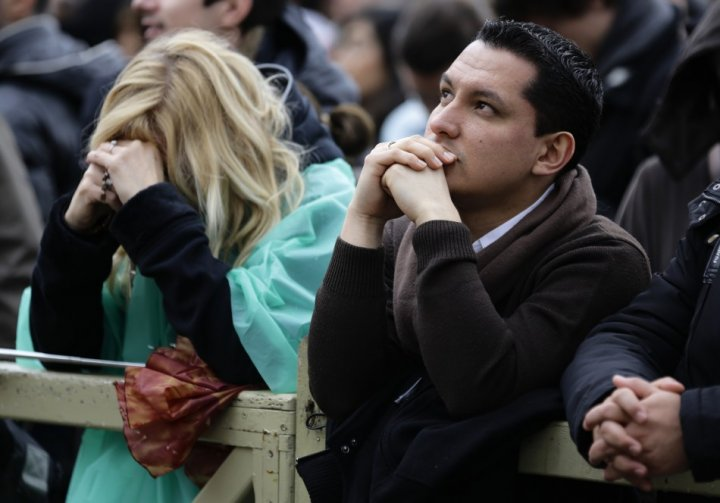 Faithful react while waiting for smoke to rise from a chimney on top of the Sistine Chapel during the second day of voting for the election of a new pope, at the Vatican March 13, 2013. Roman Catholic Cardinals will continue their conclave meeting inside