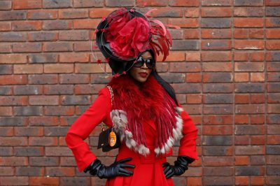 Racegoer Lystra Adams poses in her hat on Ladies Day, the second day of racing at the Cheltenham Festival horse racing meet in Gloucestershire, western England March 13, 2013.