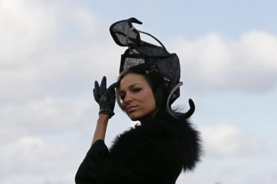 Racegoer Victoria Ilina poses in her hat on Ladies Day, the second day of racing at the Cheltenham Festival horse racing meet in Gloucestershire, western England March 13, 2013.