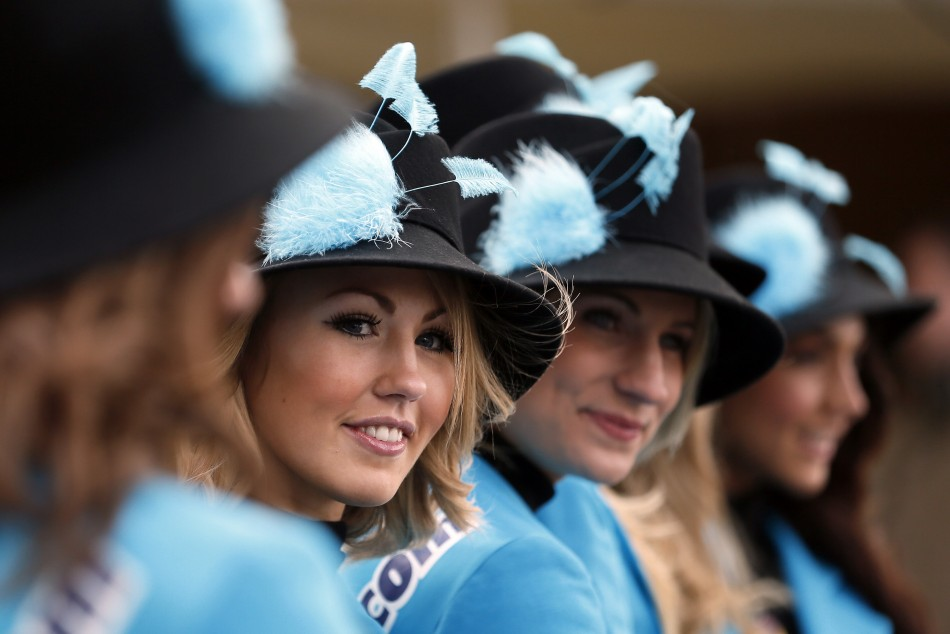 Women pose in their hats on Ladies Day, the second day of racing at the Cheltenham Festival horse racing meet in Gloucestershire, western England March 13, 2013.