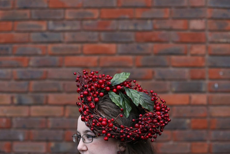 Racegoer Helen Neary poses in her hat on Ladies Day, the second day of racing at the Cheltenham Festival horse racing meet in Gloucestershire, western England March 13, 2013.