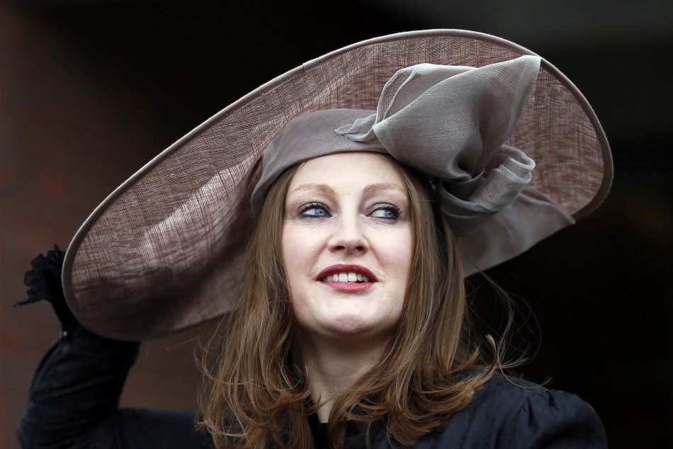 Racegoer Camilla Bassett-Smith poses in her hat on Ladies Day, the second day of racing at the Cheltenham Festival horse racing meet in Gloucestershire, western England March 13, 2013.