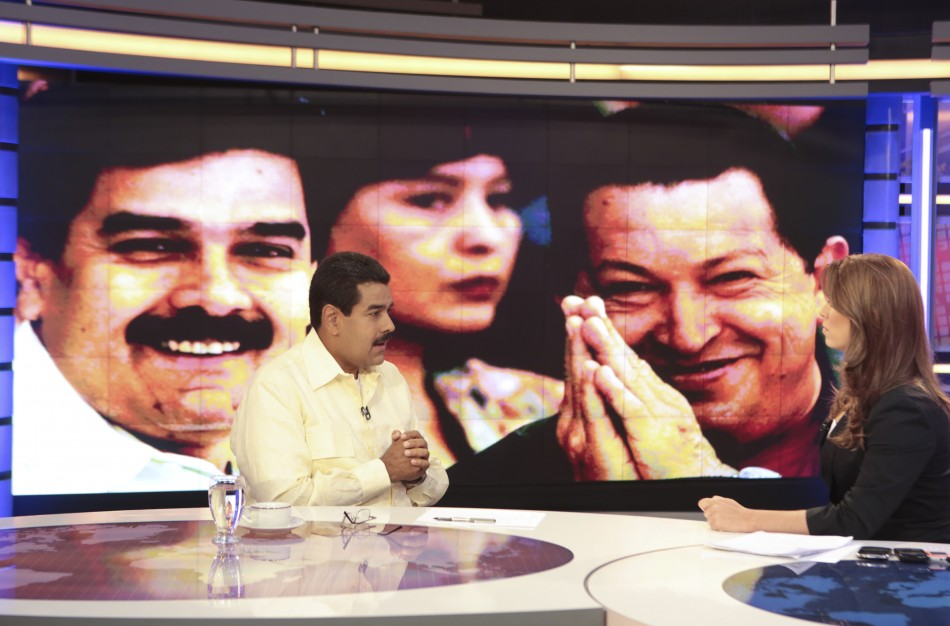 Acting Venezuelan President Nicolas Maduro (L) speaks during an interview with the news station Telesur in Caracas March