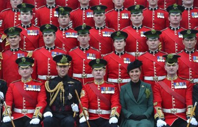 Britains Catherine, Duchess of Cambridge 2nd R and her husband Prince William 2nd L pose for an official photograph as they attend a St Patricks Day Parade at Mons Barracks in Aldershot, southern England March 17, 2013. Prince William atte