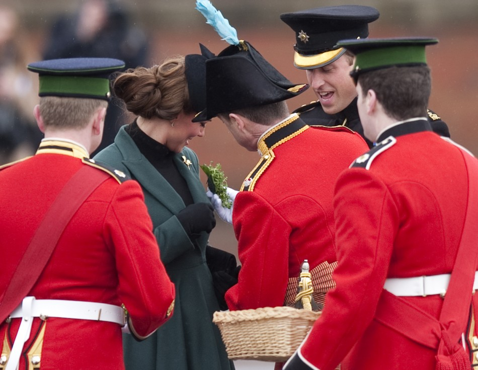 Britains Catherine, Duchess of Cambridge 2nd L is presented with a shamrock during a visit with her husband Prince William 2nd R to the 1st Battalion Irish Guards for a St Patricks Day Parade at Mons Barracks in Aldershot, southern England