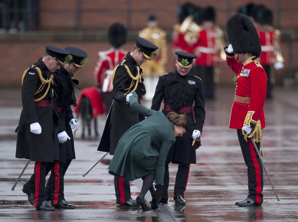 Britains Prince William C supports his wife Catherine, Duchess of Cambridge as she pulls her heel from a grate during a visit on St Patricks Day to Mons Barracks in Aldershot, southern England March 17, 2013.