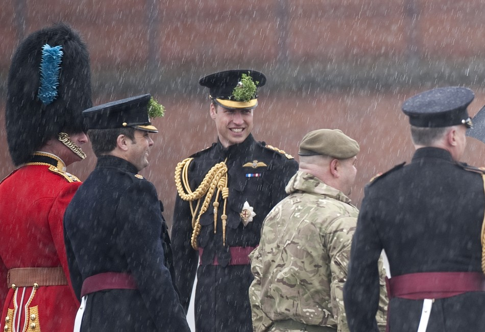Britains Prince William C stands in the rain during a visit to Mons Barracks in Aldershot, southern England March 17, 2013. Prince William attended the St Patricks Day Parade as Colonel of the Regiment, and his wife Catherine, Duchess presen